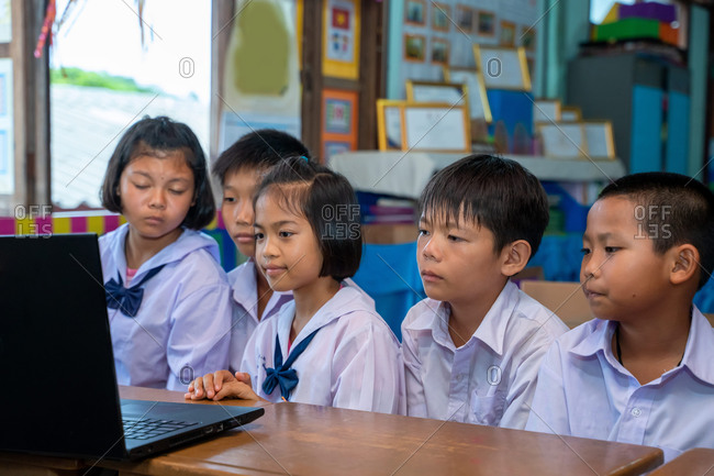 Elementary school students looking at computer in classroom