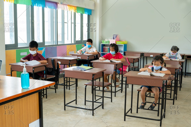 Children students wearing a coronavirus mask working at their desks
