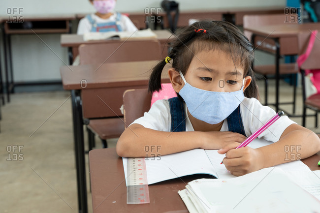 Elementary student with face mask back at school after covid-19