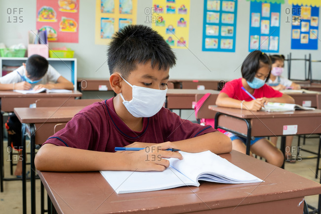 Elementary school students wearing masks study in classroom