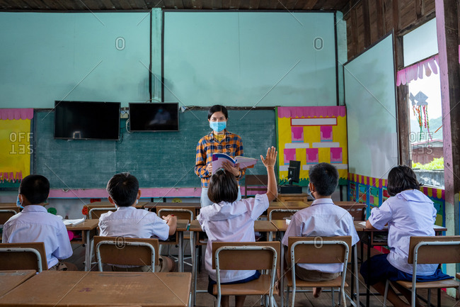 Asian children wear face masks while learning in classroom