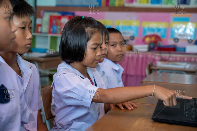Group of Asian elementary school students learning to use laptops