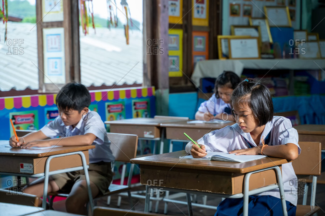 Asian elementary students in uniform studying together in classroom