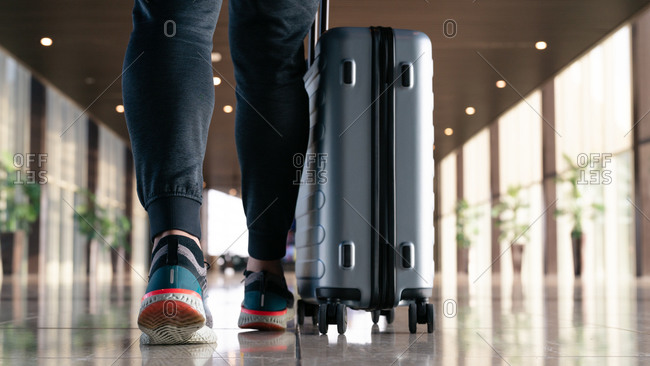 Traveler with suitcase carrying luggage