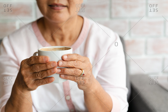 Old woman hold a cup of hot coffee drink at home