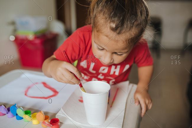 Child Finger Paints a Rainbow
