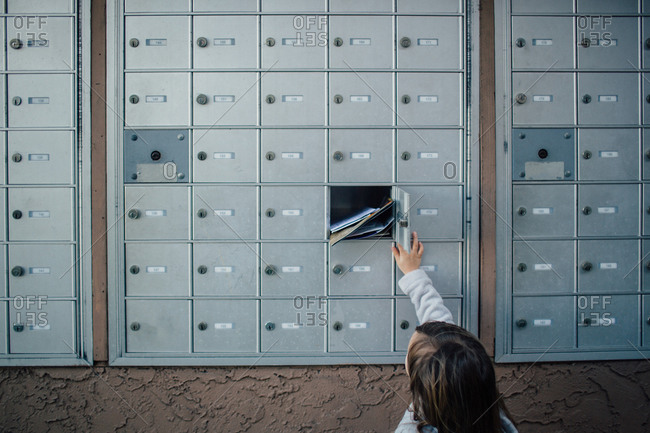 Child unlocks and opens door to cluster mailbox unit