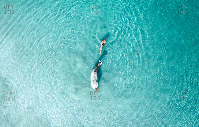 August 9, 2019: Aerial View Of Person Swimming And Playing With Horse In The Blue Ocean Waves, Tierra Bomba, Colombia