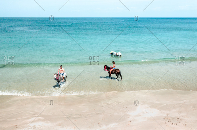 August 9, 2019: Aerial View Of People Riding And Swimming With Horses Along Tropical Island Beachfront, Tierra Bomba, Colombia