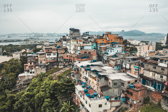 November 18, 2019: Aerial View Of Densely Packed Colored Houses Of Santo Amaro Hillside Favela, Niteroi In Distance, Rio De Janeiro, Brazil