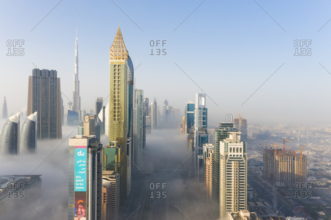 March 29, 2019: Aerial view of misty skyscrapers with highway in Dubai, United Arab Emirates.