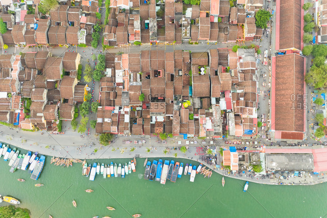 Aerial view of boats and river, over the rooftops of Hoi An, Vietnam.