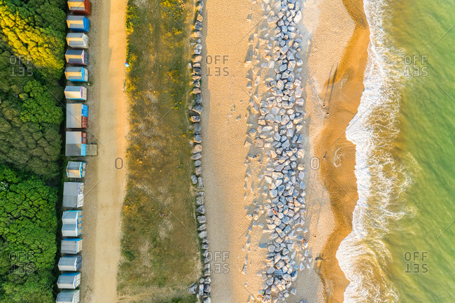 Aerial top down view of sea defense on beach and colorful beach huts near Barton-on-Sea, UK.