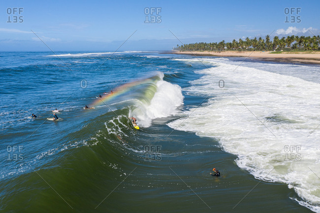 May 23, 2020: Aerial view of surfers with rainbow forming over wave close to Praia do Forte and Praia do Lord, Brazil.