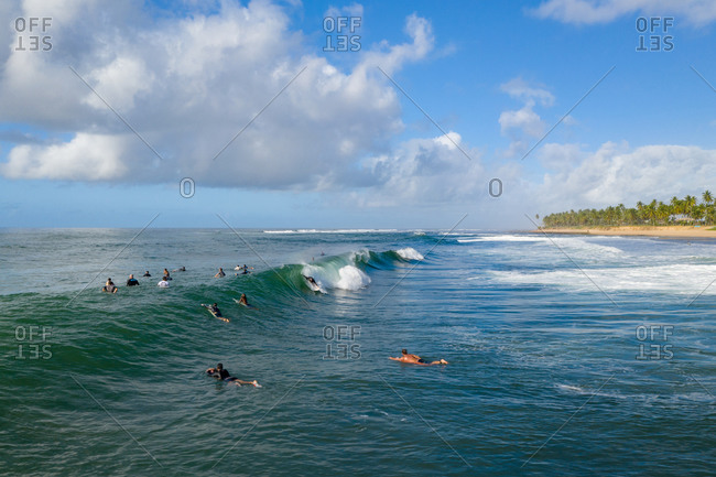 Aerial view of surfers in waves close to Praia do Forte and Praia do Lord, Brazil.