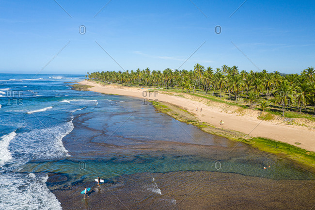 Praia do Forte, Brazil - July 1, 2020: Aerial view of surfers walking on beach towards waves close to Praia do Lord.