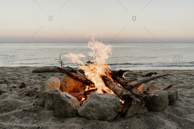 Campfire on empty beach during sunset