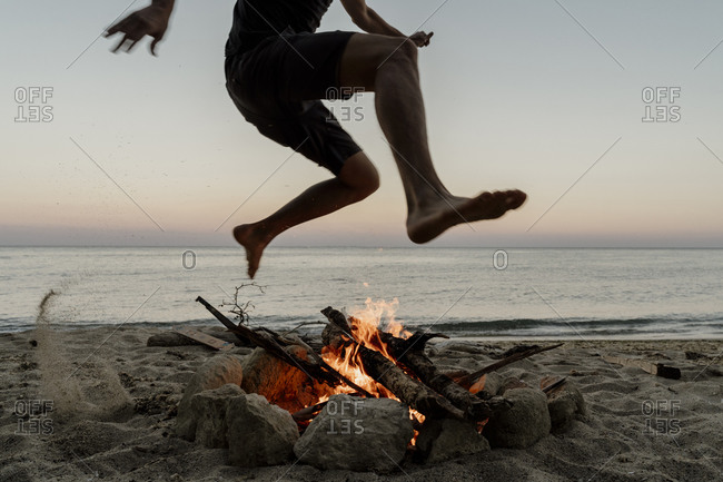 Man jumping over campfire at beach during sunset