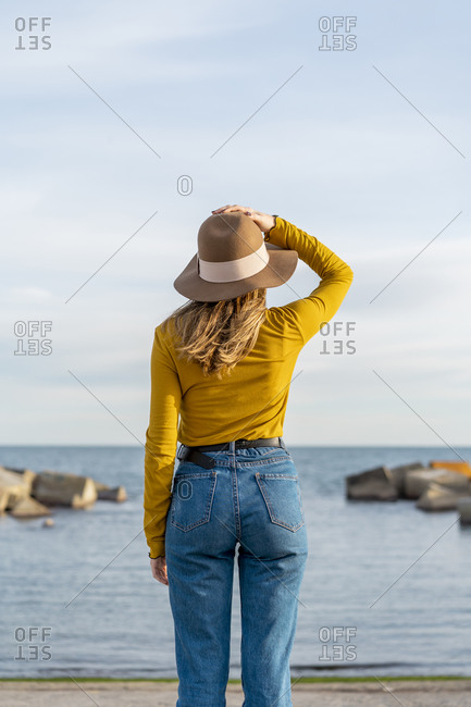 Young woman with arms raised wearing sun hat against sea