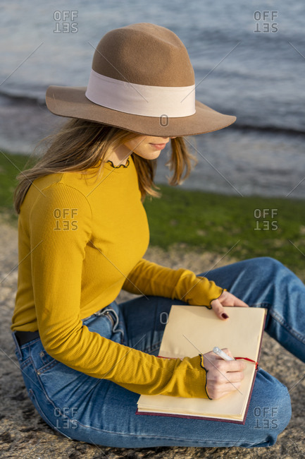 Young woman with sun hat writing in diary while sitting on ground