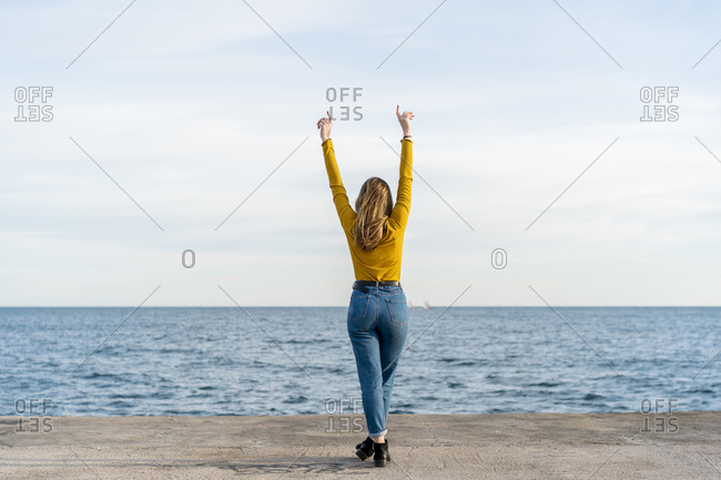 Young woman with arms raised standing against sea