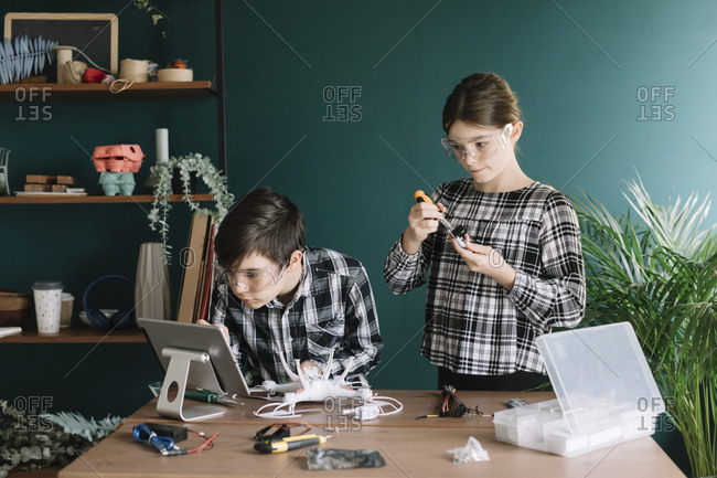 Siblings using digital tablet while preparing drone on table against wall at home