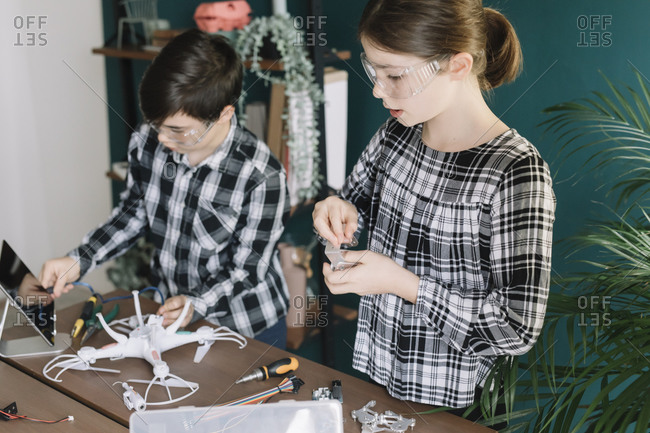 Siblings using digital tablet while preparing drone on table at home