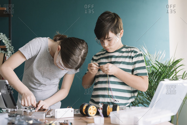 Siblings making robotic toy on table at home