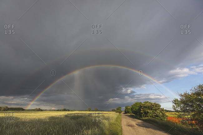 Scenic view of rainbow over agricultural landscape against cloudy sky