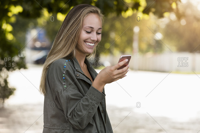 Smiling young woman using smart phone while standing in park
