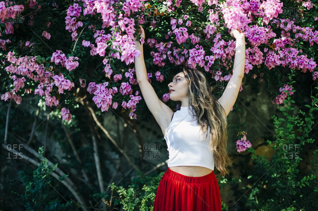 Beautiful woman with arms raised standing against flowers in park