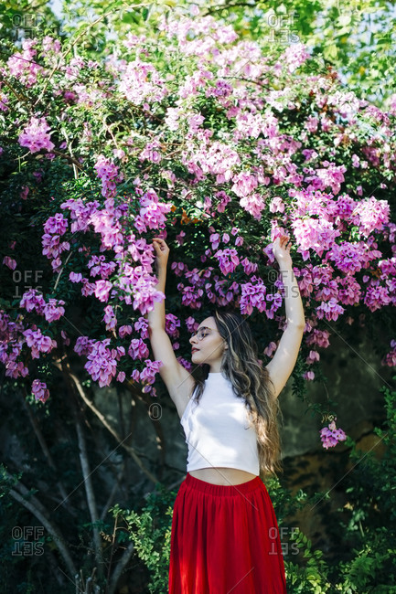 Young woman with arms raised standing against plants in park