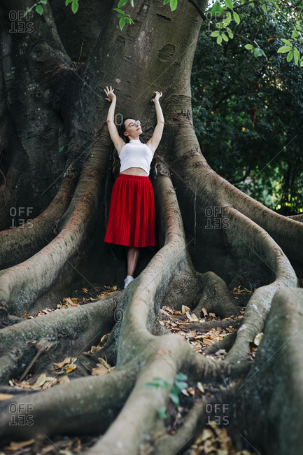 Young woman with arms raised leaning on tree trunk in park