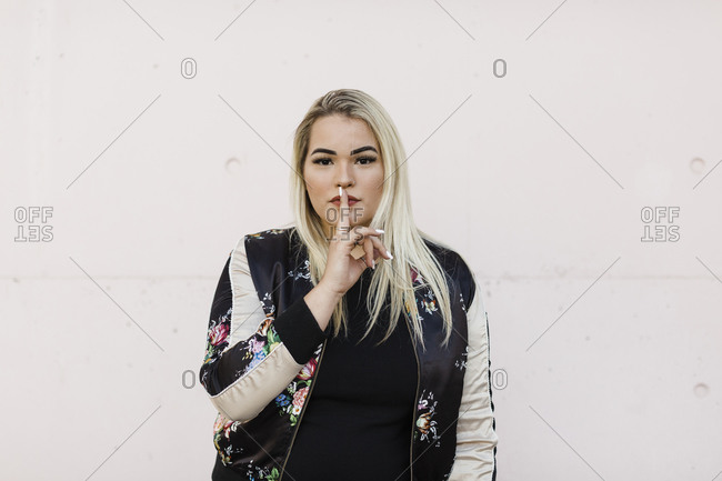 Young woman with finger on lips standing against wall