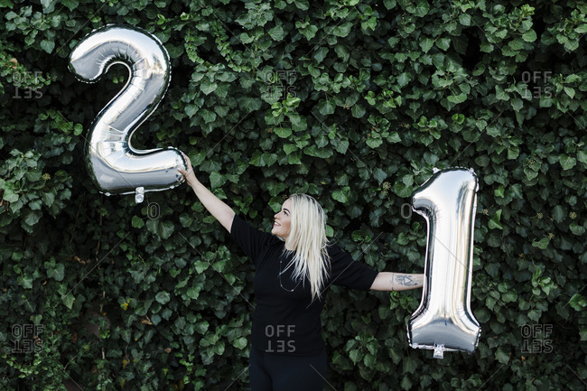 Young woman with arms outstretched holding number 21 balloons against plants in park