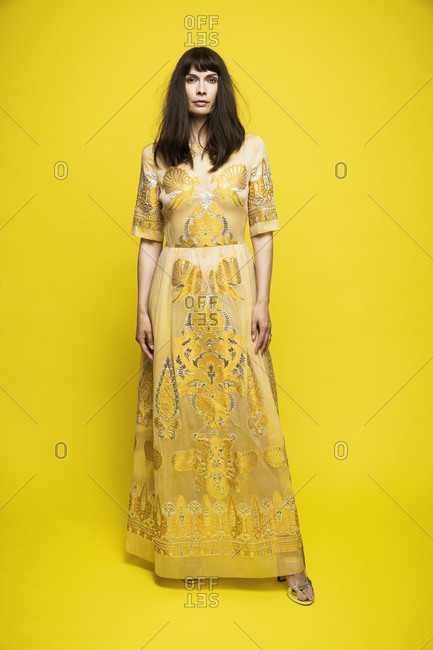 Mature woman wearing dress standing against yellow background