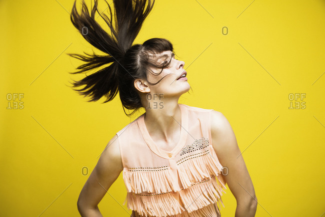 Fashion model tossing hair while standing against yellow background