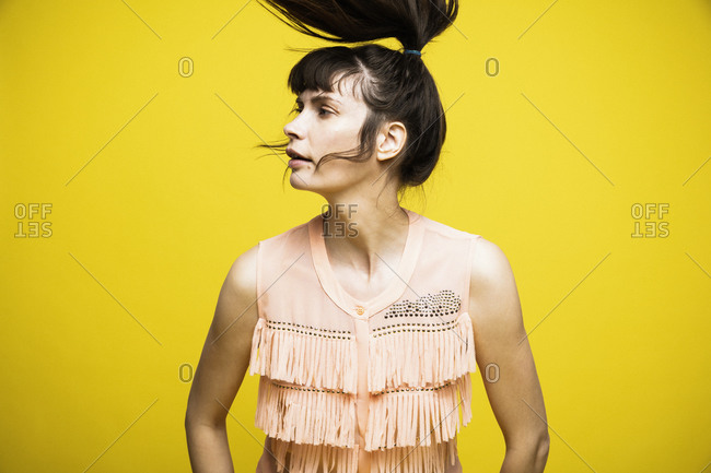 Woman tossing hair while standing against yellow background