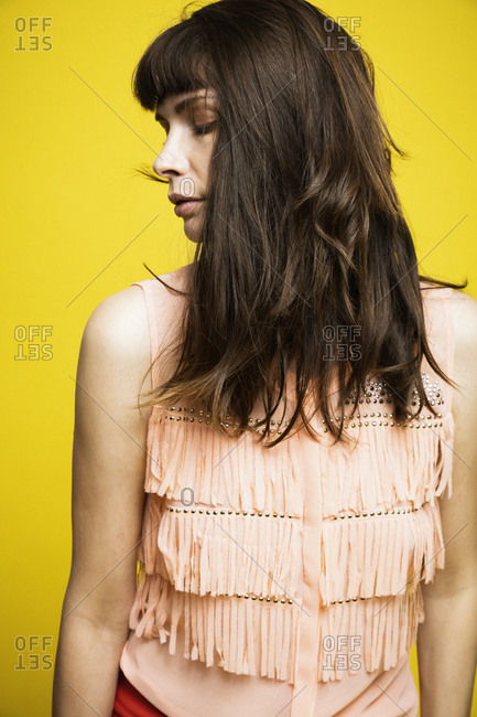 Close-up of beautiful woman with eyes closed against yellow background