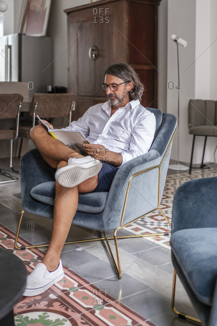 Man reading book while sitting on armchair at home