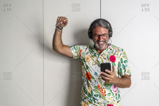 Smiling man with hand raised using mobile phone against closet