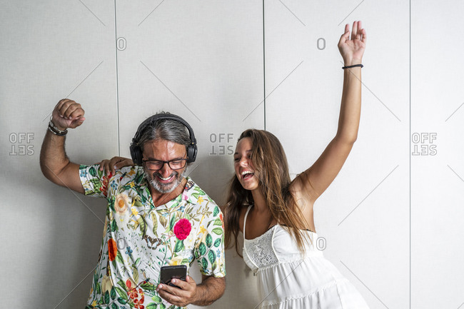Smiling father and daughter cheering while standing against closet