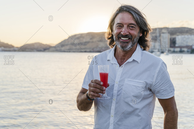 Smiling mature man holding drink while standing against sea during sunset