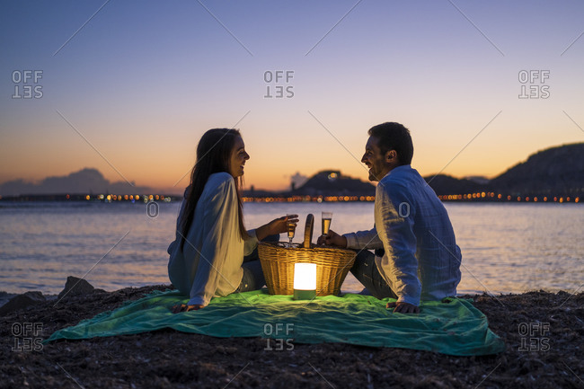 Couple with drinks looking at each other while sitting on beach against clear sky during dusk