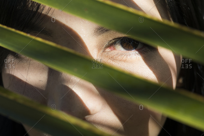 Close-up of mid adult woman seen through leaves