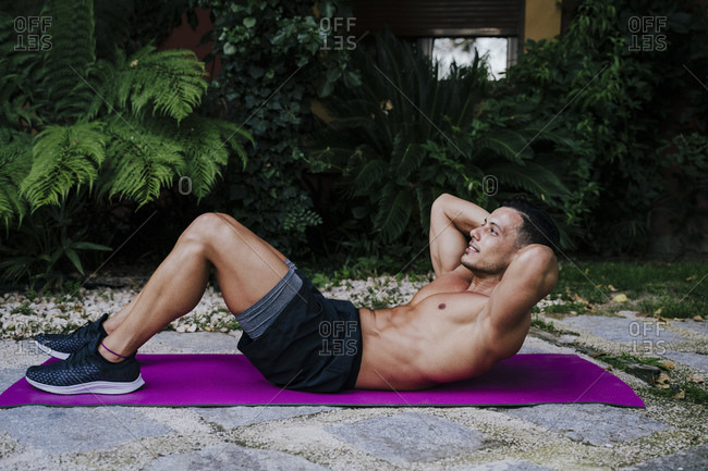 Shirtless athlete with hands behind head exercising on mat against plants in yard