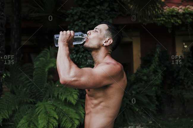 Shirtless male athlete drinking water while standing against plants in yard