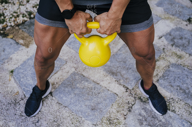 Mid adult man lifting kettlebell while standing in yard