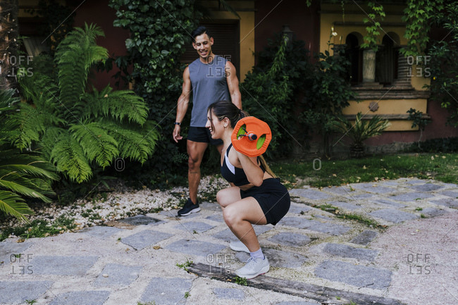 Fitness instructor looking at woman lifting weights in yard