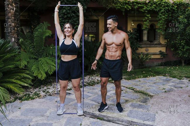 Fitness instructor looking at woman exercising with strap in yard